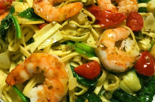 Shrimp with fresh vegetables and pesto served over pasta